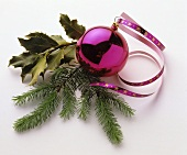 Pink Christmas bauble with sprigs of fir and holly