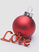 Red Christmas bauble and the word Love