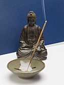 Incense stick in ceramic dish in front of Buddha figure