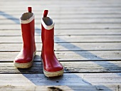 Red wellingtons on wooden landing stage
