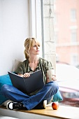 Blond woman sitting by window with a book