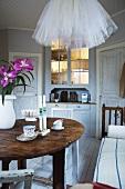 Traditionelles Esszimmer mit origineller, weisser Tülllampe über Vintage-Esstisch