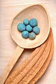 Bath pearls on wooden spoon, loofah plant