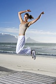 South Africa, Cape Town, Young woman jumping on beach