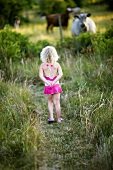 Girl watching cows in pasture