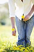 Woman with dandelions in a field of dandelions