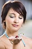 Junge Frau hält eine Kirsche auf der Hand