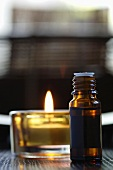 Bottle of scented oil, beside a tealight, close-up