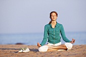 Young woman meditating on beach