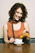 Woman dipping croissant into cup of coffee