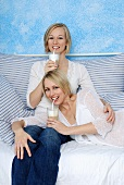 Two women on sofa drinking white coffee