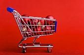 Rote Christbaumkugeln mit Einkaufswagen