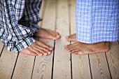 Two pairs of feet in pyjamas