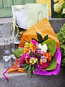 Bouquet of summer flowers, bottles & shopping bag on doorstep
