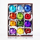 Several shiny, coloured Christmas baubles in box