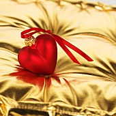 Red heart (tree ornament) on gold cushion