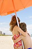 Two children under sunshade on sandy beach (Brazil)