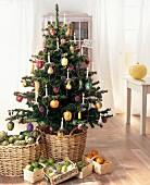 Weihnachtsbaum mit Schmuck in Obstform und mit Kerzen, davor Früchte in Körben auf dem Boden