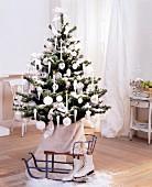 Weihnachtsbaum mit weißen Kugeln und Kerzen dekoriert, davor Vintage Schlitten und Schlittschuhen auf Holzboden