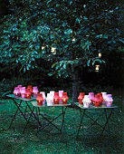 Multicoloured lit lanterns on tables and in trees in twilit garden