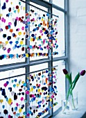 A multi-coloured beaded curtain against window
