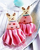 Bunny-shaped biscuits decorated with fondant icing and icing sugar