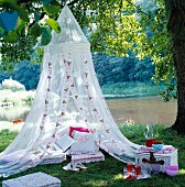 Floor cushions and decorative cushions under a romantic mosquito net by a lake