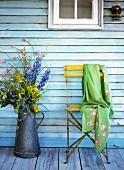 Wiesenblumen in Zinkkanne und Gartenstuhl mit bestickter Kaschmirschal vor Hauswand
