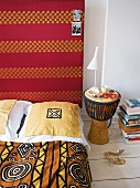 An ethnic-style bedroom with patterned bedclothes and a drum as bedside table