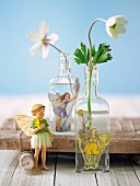 Anemones in glass bottles decorated with fairy stickers with a fairy figurine