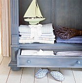 Linen, a decorative ship and a bundle of lavender in a purple wooden dresser
