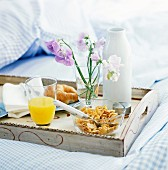 A croissant, cornflakes and orange juice on a breakfast tray