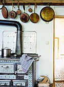 Row of pans hung above antique wood-burning cooker in country-house kitchen