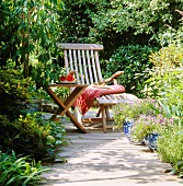 A wooden lounger and a table in a summery garden