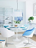 A dining area in white with a round table, bucket chairs and touches of blue