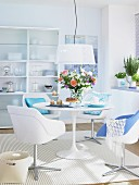A dining room in white with a round table, bucket chairs and touches of blue