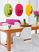 A long wooden dining table with white panton chairs and colourful, oriental-patterened paper lanterns