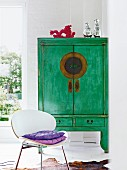 Green, wooden Chinese wedding cabinet and white shell chair