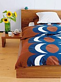 Retro bedspread and sunflowers in vase on side table