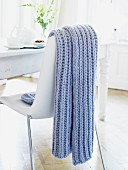 A blue knitted throw hanging over the back of a chair