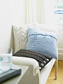 Three knitted cushions on large chair