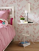 White-painted metal side table next to bed in bedroom with pink and white floral wallpaper