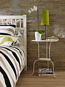 White-painted, metal side table next to bed in bedroom with stone-effect wallpaper