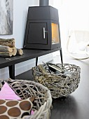 Two wicker baskets below cast iron stove on bench
