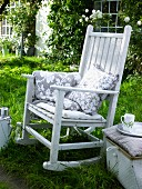 White rocking chair with cushions in garden