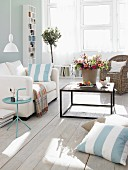 Living room in pastel shades, white couch and vase of flowers on coffee table