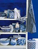 Weisses Holzregal mit Geschirr in Weiss und Blau in ländlichem Stil vor blau getönter Wand