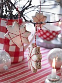 Star-shaped cinnamon biscuits hanging from twig as Christmas decorations