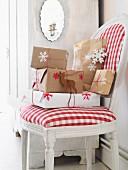 Verpackte Weihnachtsgeschenke auf Polsterstuhl mit rot-weiss kariertem Bezug