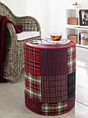 A cup of tea on a red-checked patchwork pouffe in a living room